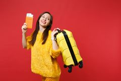 Pretty young woman in yellow fur sweater looking aside, holding suitcase, passport boarding pass ticket isolated on red. Wall background. People sincere royalty free stock image