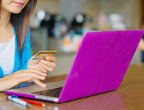 Pretty Young womans hands holding a credit card and using laptop computer for online shopping. Stock Image