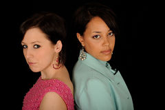 Pretty young women. Close up of African American and caucasian women standing back to back and looking over shoulder, black background Stock Photography