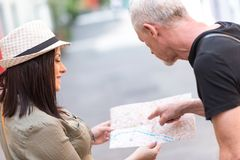 Pretty young woman asking for direction. Pretty young women asking for direction on city map royalty free stock photo