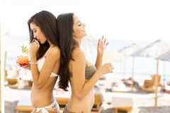 Pretty young women with coctails on the beach Royalty Free Stock Photos