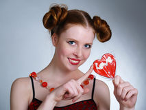 Pretty young women holding heart shaped lollipop Royalty Free Stock Photo