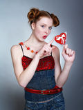 Pretty young women holding heart shaped lollipop Royalty Free Stock Images
