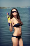 Pretty young women playing water gun Stock Images