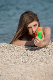 Pretty young women playing with water gun at the beach. Pretty young woman with slim and long blond hair playing with water gun at the beach, lie prone, taking royalty free stock images