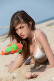 Pretty young women playing with water gun at the beach. Pretty young woman with slim and long blond hair playing with water gun at the beach, lying prone on sand Stock Images