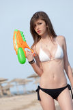 Pretty young women playing with water gun at the beach. Pretty young woman with slim and long blond hair playing with water gun at the beach, organized beach royalty free stock photography
