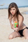 Pretty young women playing with water gun at the beach. Pretty young woman with slim and long blond hair playing with water gun at the beach, sitting on sand royalty free stock photography