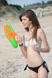 Pretty young women playing with water gun at the beach. Pretty young woman with slim and long blond hair playing with water gun at the beach, standing in profile stock photo