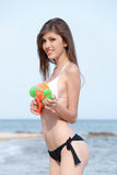 Pretty young women playing with water gun at the beach. Pretty young woman with slim and long blond hair playing with water gun at the beach, standing in profile royalty free stock photography