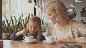 Woman puts spoon into the daughter`s cup at the cafe. Pretty young women putting spoon into the her daughter`s cup. Attractive little girl beginning to stir stock photo