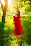 Pretty young women in red dress backlit by sunset in front of green trees. Royalty Free Stock Image