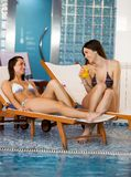Young women by the pool Royalty Free Stock Photos