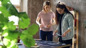 Young women are standing near table, placing pictures on it and shooting flat lay with smartphone. They are sharing. Pretty young women are standing near table stock video