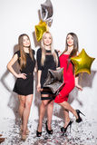 Pretty young women with star shaped balloons and confetti dancing and having party Stock Image