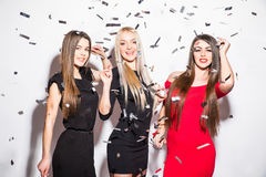 Pretty young women with star shaped balloons and confetti dancing and having party Royalty Free Stock Images
