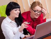 Pretty young women at workplace Stock Photos