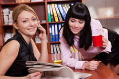 Pretty young women at workplace Stock Image
