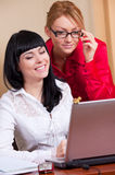 Pretty young women at workplace Stock Photography