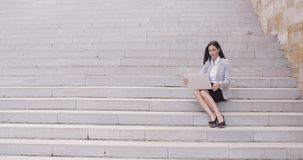 Pretty young worker sitting on steps with laptop stock footage