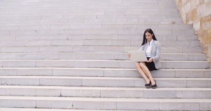 Pretty young worker sitting on steps with laptop Stock Photos