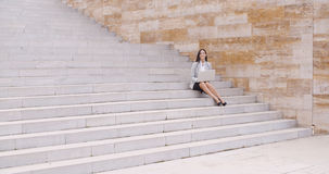 Pretty young worker sitting on steps with laptop Royalty Free Stock Photo