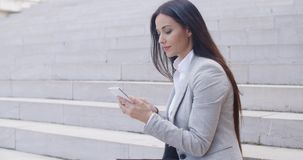 Pretty young worker sitting on steps with phone stock video footage