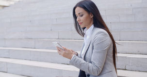 Pretty young worker sitting on steps with phone Stock Photos