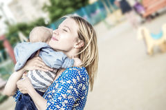 Prettyl happy mather with baby boy Embracing him emotionally on a liking stock photos