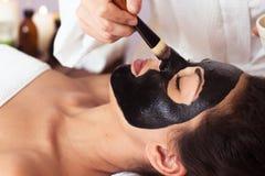 Prettyl kobieta z twarzową maską przy piękno salonem w spa Obrazy Royalty Free