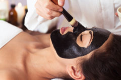Prettyl woman with facial mask at beauty salon. Spa treatment Royalty Free Stock Images
