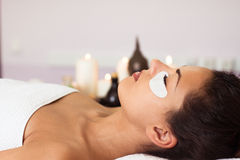 Prettyl woman with facial mask at beauty salon. Spa treatment Stock Image