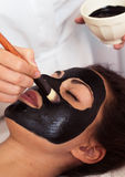 Prettyl woman with facial mask at beauty salon. Spa treatment Stock Photos