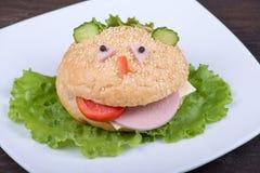 Pretvoedsel voor jonge geitjes - de hamburger kijkt als een grappige snuit Stock Afbeelding