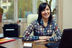 Prety friendly woman sitting in office. Attractive friendly woman sitting in workplace. office interior Stock Photos