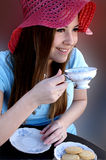 Prety girl sipping tea from porcelin tea cup. Pretty girl's face framed with red hat sipping tea from Bavarian porcelin tea cup with cookies on matching plate Stock Photos