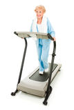 Prety Senior Stays Fit. Beautiful senoir woman staying fit by walking on a treadmill.  Isolated on white Royalty Free Stock Photography