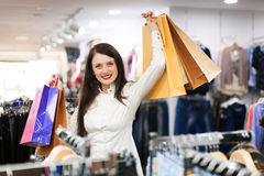 Prety young woman with a lot of shopping bags. At fashionable store Royalty Free Stock Photography
