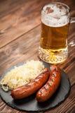 Pretzeis, bratwurst e chucrute na tabela de madeira imagens de stock