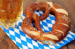 Pretzel on bavarian tablecloth. Beer glass aside with silverware on table Stock Images