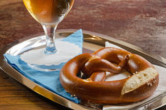 Pretzel and beer glass on blue and white serviettes. A close-up of a glass of cold beer and a pretzel served on a metal tray with white and blue serviettes on an Stock Images