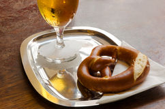 Pretzel and beer glass on a metal tray with a white serviette. Pretzel and a glass of cold beer with a drop catcher on a metal tray with a white serviette Stock Photography