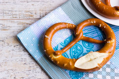 Pretzel on the blue waffle towel. Bavarian pretzel for breakfast on a wooden table Stock Photos