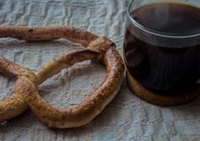 Pretzel and cup of coffe on tablecloth. A pretzel and cup of coffe on tablecloth Royalty Free Stock Image