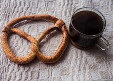 Pretzel and cup of coffe on tablecloth. A pretzel and cup of coffe on tablecloth Royalty Free Stock Photography