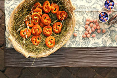 Pretzel on dried hay and some Easter chocolate balls Royalty Free Stock Photos