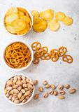 Pretzel en chips en pistache in witte ceramische kom op de lijstachtergrond van de steenkeuken Snack voor bier royalty-vrije stock foto's