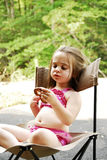 Pretzel Girl. Cute little girl eating a big pretzel in an outdoor setting Royalty Free Stock Photography