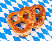 Pretzel in heart shape on white blue background Royalty Free Stock Photo
