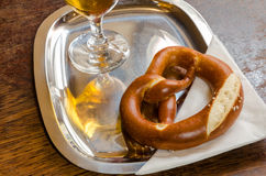 Pretzel on a metal tray with the reflection of the beer glass. Pretzel and a glass of cold beer with a drop catcher on a metal tray with a white serviette Stock Photos